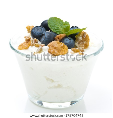 fresh yogurt  with muesli and blueberries in a glass, close-up, isolated on white