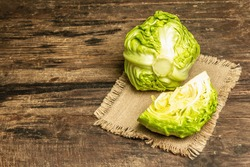 Fresh young cabbage in a rustic arrangement. Vintage boards table, sackcloth napkin