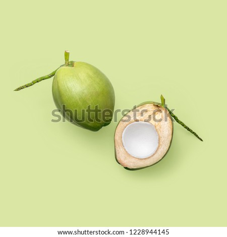 Fresh young coconuts on a green background, creative flat lay healthy food concept, top view with clipping path