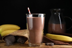 Fresh yummy chocolate milk on wooden table