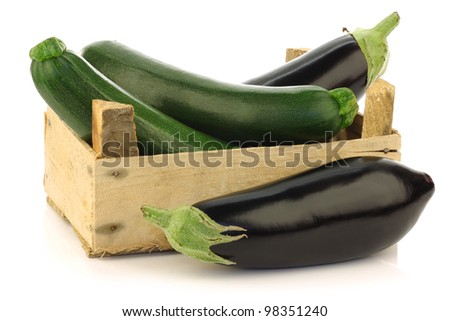 fresh zucchini's (Cucurbita pepo) and eggplant in a wooden box on a white background