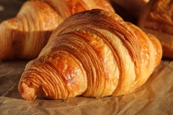 Freshly backed french croissant shiny in the rays of the morning  sun.