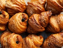 Freshly backed french traditional pastry - chocolate croissants shiny in the rays of the sun.
