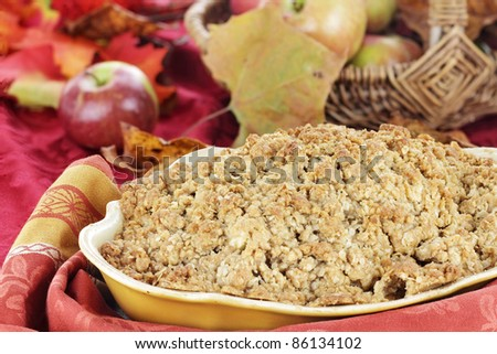Freshly baked apple crisp with fresh apples and autumn leaves in the background. Shallow depth of field with selective focus on the foreground.