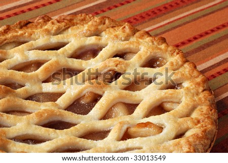 Freshly baked apple pie on colorful tablecloth.  Macro with shallow dof.