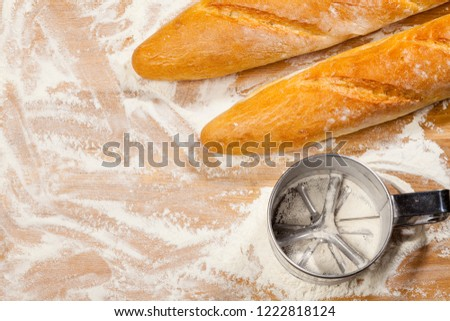Freshly baked artisanal baguettes  (french bread) with flour sieve or sifter on wooden background covered with flour