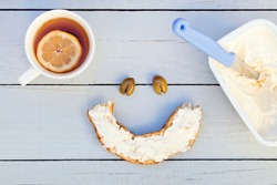 Freshly baked bagel with cream cheese and tea. Smiley face.