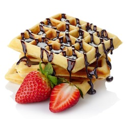 Freshly baked belgium waffles with chocolate sauce and strawberries isolated on white background
