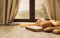 Freshly baked bread on a chopping board on the kitchen table in front of a window, healthy eating concept