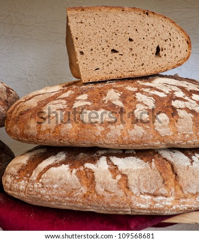 Freshly baked bread. One of them is sliced.