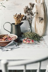 Freshly baked cherry Clafoutis dessert with vintage tableware. Slice of seasonal fruit tart with cherries. Traditional french pie with rustic, country style decor. Baker kitchen interior.