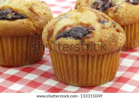 freshly baked cherry muffins on a red and white checkered table cloth