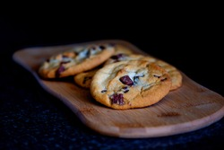 Freshly baked chocolate chip cookies on a wooden platter with a black background for brunch
