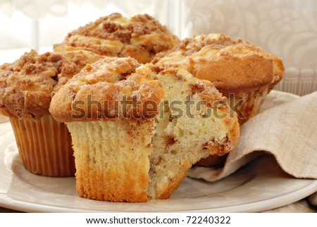 Freshly baked cinnamon muffins with sunlit window in background.  Closeup with shallow dof.