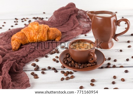 Freshly baked croissant and cup of coffee with milk on white wooden background. Fresh delicious pastries for breakfast.