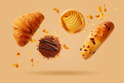 Freshly baked croissant and sweet pastries flying in air. Sweet dessert. Baked goods.