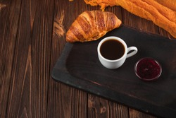 Freshly baked croissant with cup of coffee on brown wooden background. Fresh pastries for breakfast in modern dark mood style.
