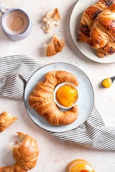 Freshly baked croissants, apricot jam and mug with cappuccino on beige stone table. French styled breakfast flat lay, top view