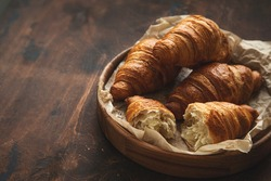 Freshly baked croissants, dark wooden background,  selective focus, toned, copy space