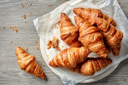 freshly baked croissants on grey wooden table, top view