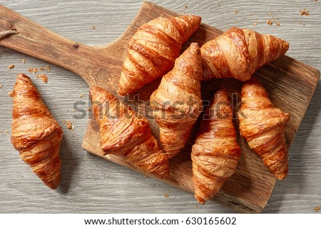 freshly baked croissants on wooden cutting board, top view Сток-фото ©