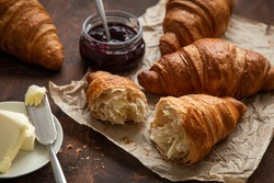 Freshly baked croissants with berries jam and butter, dark wooden background,  selective focus