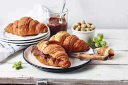 Freshly baked croissants with chocolate cream on a white rustic table.