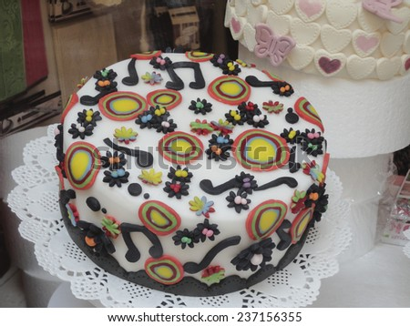 Freshly baked delicious artistic Italian Arts and Crafts cake decorated with music notes and colorful circles on white marzipan icing.