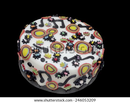 Freshly baked delicious artistic Italian Arts and Crafts cake decorated with music notes and colorful circles on white marzipan icing, high angle view isolated on a dark background