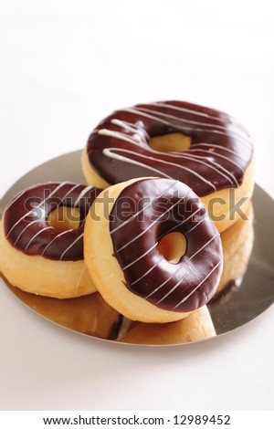 Freshly baked delicious chocolate donuts on a shiny plate.  White background, not isolated.