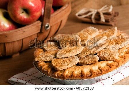 Freshly baked farmhouse apple pie with trug filled with fruit in background