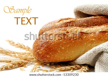 Freshly baked french bread with homespun fabric and wheat spikes on white background.