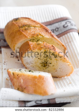 Freshly baked garlic bread with herbs close up. Selective focus