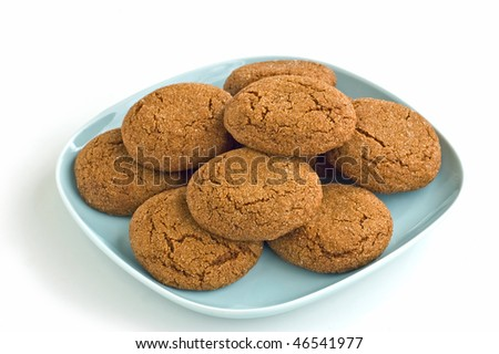 Freshly baked ginger snaps on pale blue plate isolated on white background