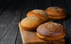 Freshly baked hamburger buns with sesame on dark wooden background. Round bun with sesame or bread rolls. Closeup