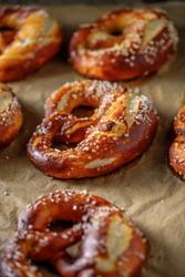 Freshly baked home soft pretzel with salt on craft paper for baking