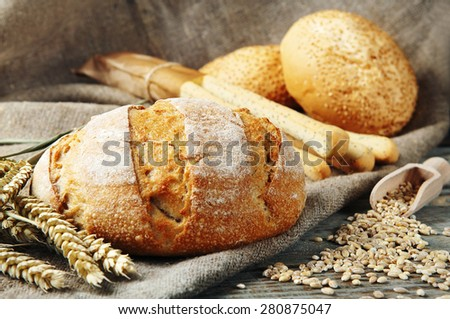 freshly baked, homemade bread on a wooden table. Next to the bread two whole eggs, scattered the seeds of wheat, two buns with sesame seeds and bread sticks with poppy seeds. rustic style. closeup