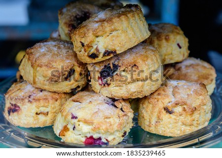 Freshly baked homemade English scones with dried fruits, displayed as a pyramid, available for sale at a café in London, side view of healthy food photographed with soft focus Stock photo ©