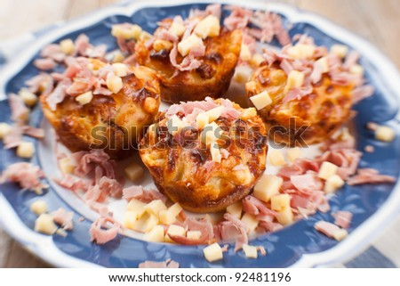 Freshly baked, homemade ham and cheese muffins. Served in a white and blue platter and decorated with ham and cheese bits