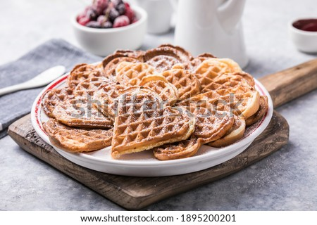 Freshly baked homemade heart shaped Belgium waffles  on gray background. European baked pastry sweets.  St. Valentine's Day breakfast concept. Stock fotó ©