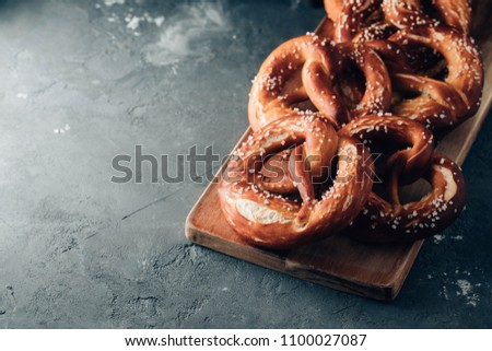 Freshly baked homemade soft pretzel with salt on rustic table. Perfect for Octoberfest. Toned image.