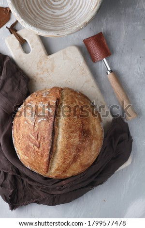 Freshly baked homemade sourdough bread with banetton and bread lame knife Photo stock ©