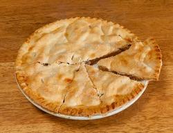 Freshly baked hot apple pie on wooden table
