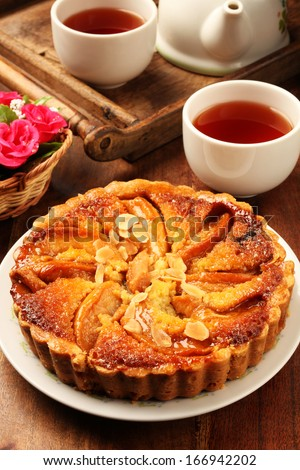 Freshly baked hot apple pie served on a white plate with tea