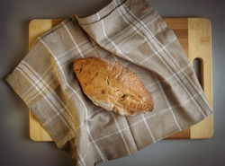 Freshly baked, hot country bread with flour, freshly from the oven on a brown linen towel with white squares, a wooden board. Appetizing photography. It resembles an American football ball in shape.
