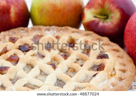 Freshly baked lattice apple pie with apples in the background
