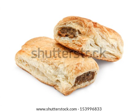 Freshly baked pair of sausage rolls isolated against a white background a traditional popular pastry snack available hot or cold at bakeries in the UK