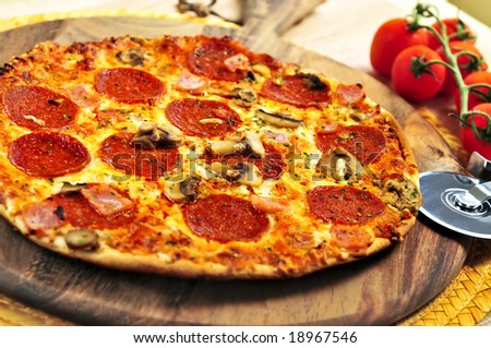 Freshly baked pepperoni pizza on wooden board
