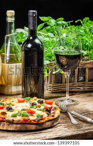 Freshly baked pizza served with red wine