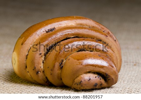 Freshly  baked poppy bun over sacking - stock photo